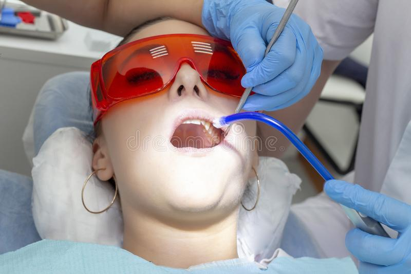 Girl patient at the reception at dentist. treatment of carious tooth. the girl lies on the dental chair with his mouth open. A den royalty free stock photo