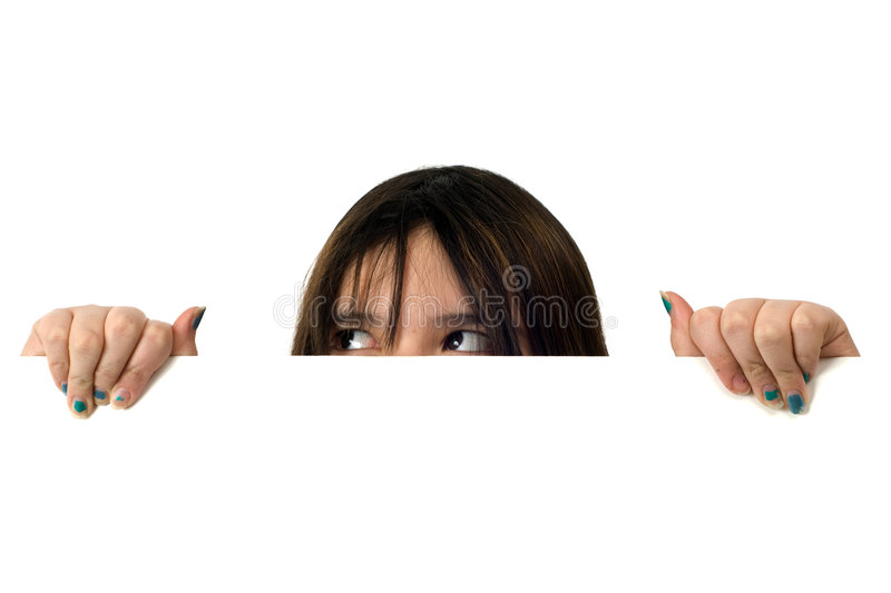Girl Peeking. A young girl peeking over a white wall with her eyes looking at an upper corner stock image