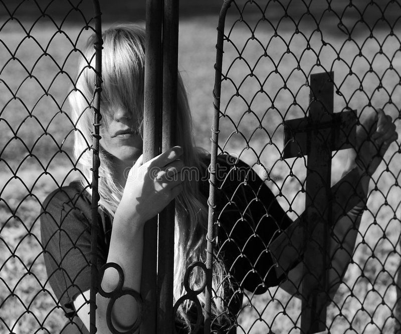 Girl peeking from behind gate royalty free stock image