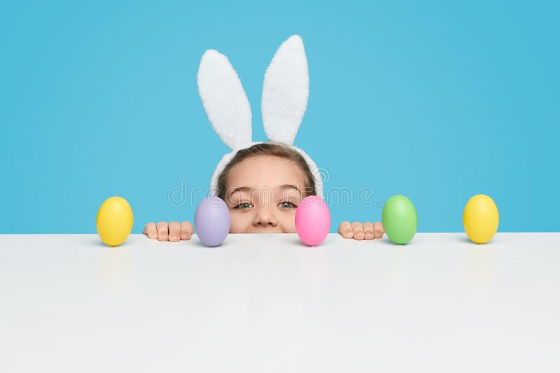 Girl with peeking out from behind table with Easter eggs. Cute little girl with white bunny ears looking at camera while peeking out from behind table with stock image