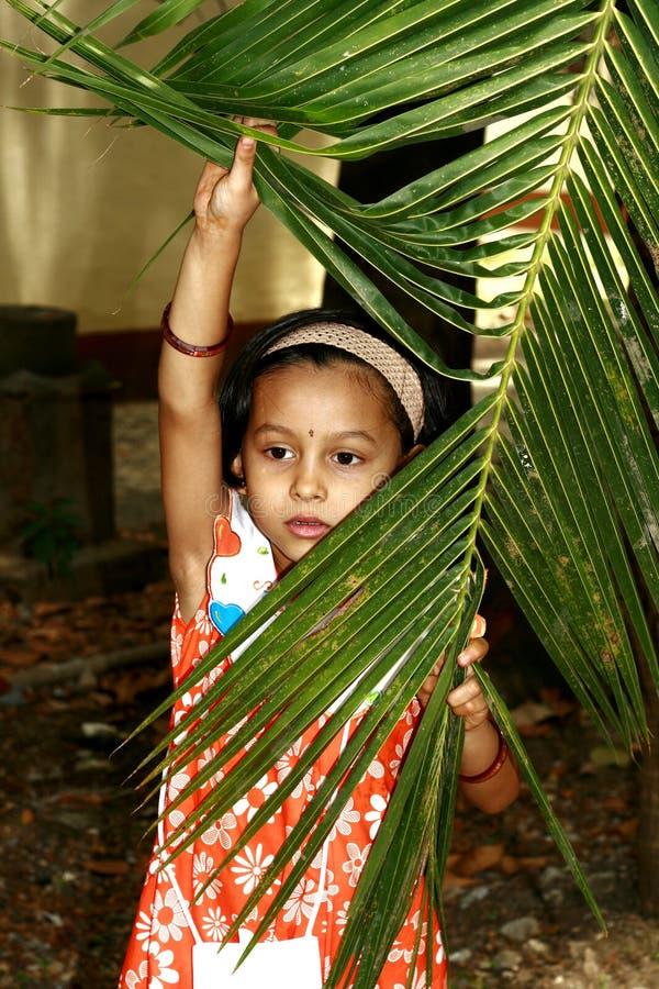 Girl peeking through palm