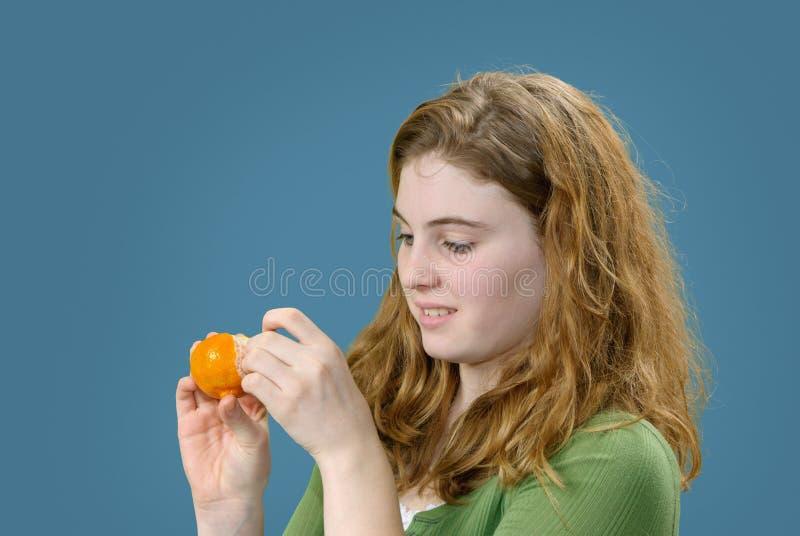 Girl Peeling Tangerine royalty free stock photos