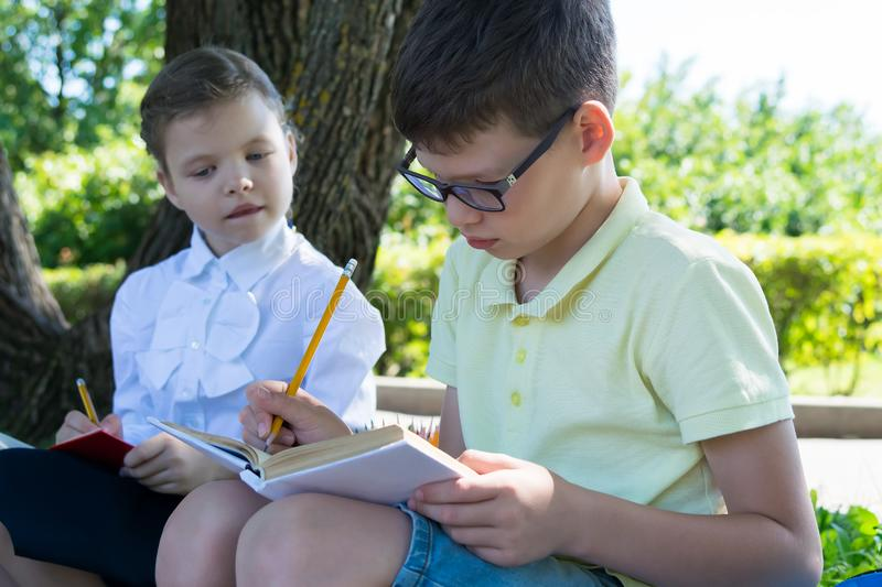 Girl peeps into the textbook to the boy how to do the assignment from the teacher royalty free stock photo