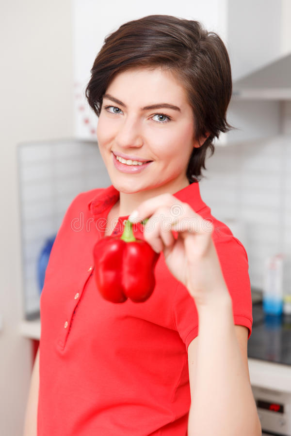 Girl with pepper in hand. At kitchen stock photo