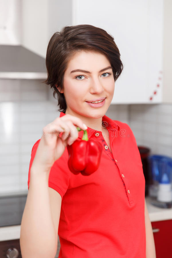 Girl with pepper in hand. At kitchen stock image