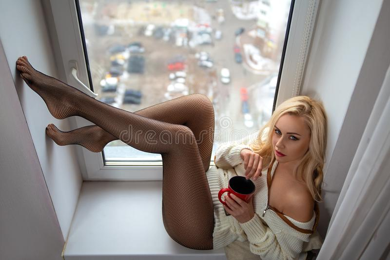 Girl with perfect legs in pantyhose posing on the windowsill royalty free stock images