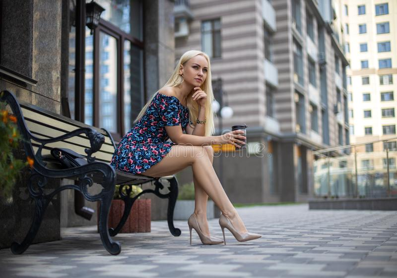 Girl with perfect legs posing in the city square royalty free stock images
