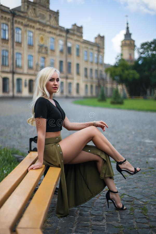 Girl with perfect legs sitting at the city square royalty free stock photo