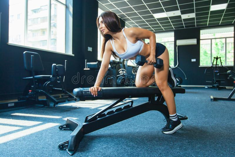 A girl performs a dumbbell with one hand in the slope using a bench. exercise on the broadest back muscles with royalty free stock images
