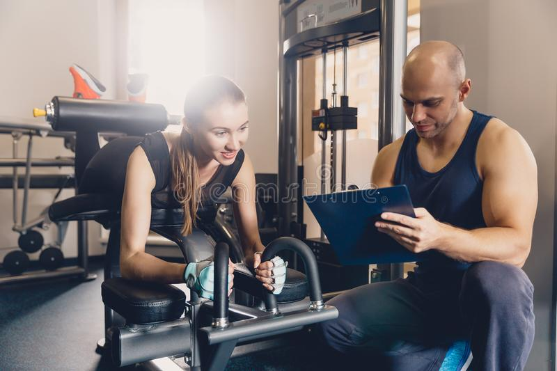 Girl performs training with an individual trainer. Individual training with a trainer on the simulator to improve the strength of the muscles. Sports program royalty free stock photography