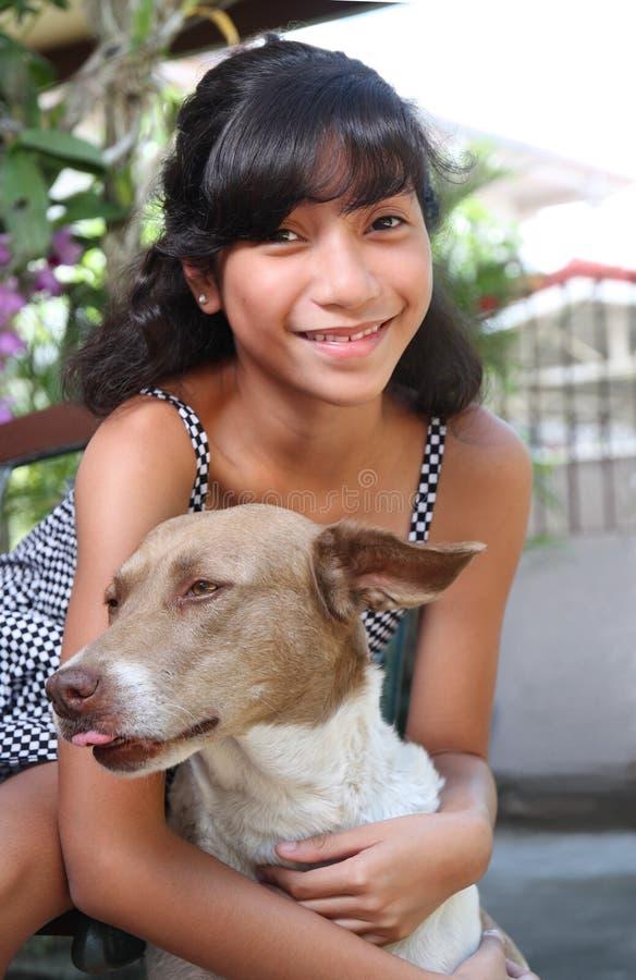 Girl with pet dog. Young asian girl hugging a pet dog stock photos