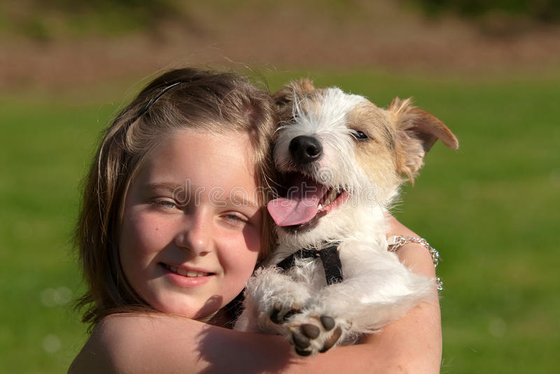 Girl with pet dog. Portrait of young girl cuddling pet dog, grass in background stock photos