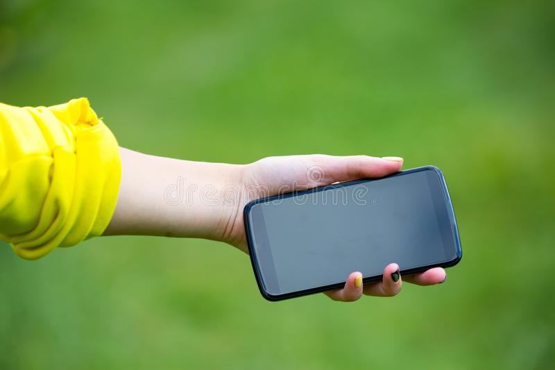 A girl with a phone in her hand outdoors stock image