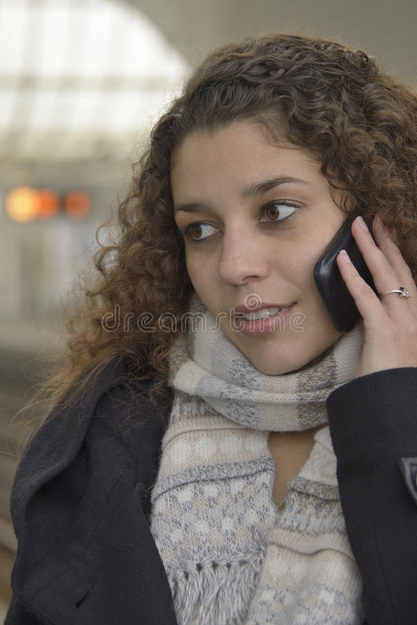 Girl phoning in train station stock photography