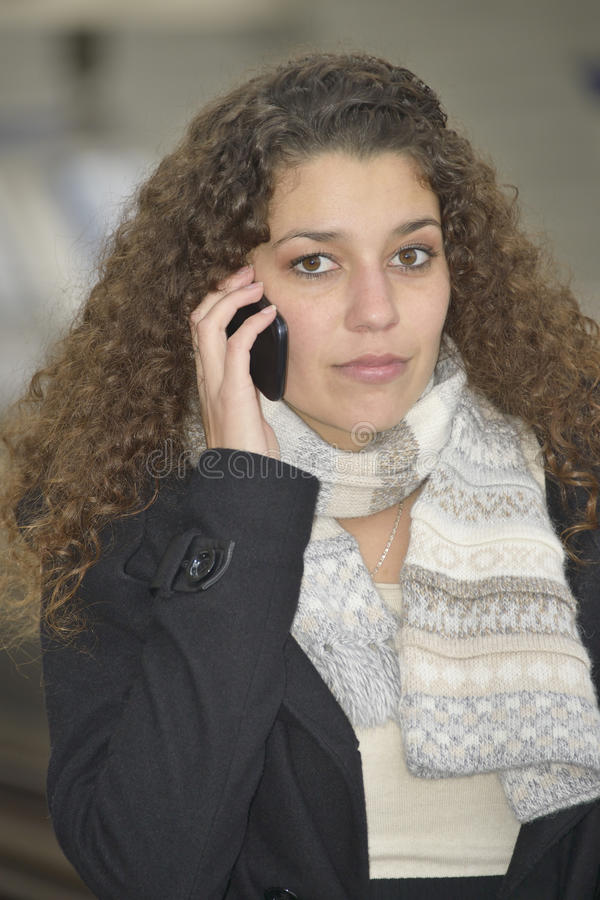 Girl phoning in train station stock photo