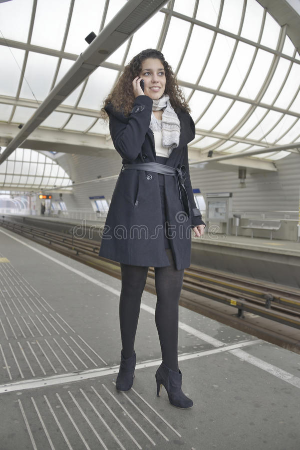 Girl phoning in train station stock images