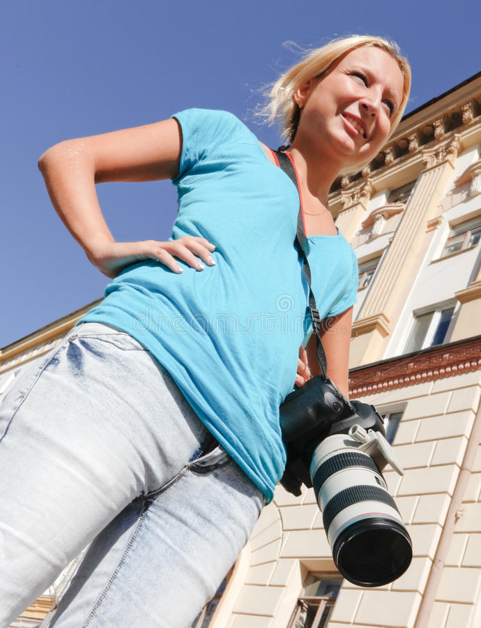 Girl-photographer. With a camera in the urban landscape stock photography