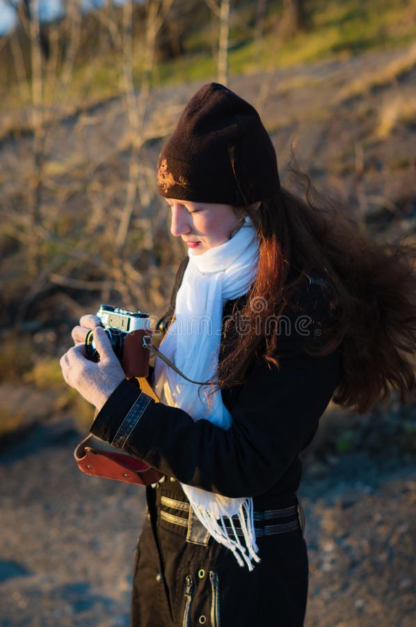 Girl photographer with an old camera taking pictures stock photos
