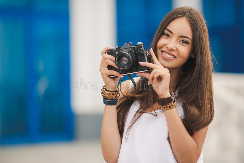 Girl photographer with professional SLR camera. Female photographer with professional SLR camera, natural light, selective focus on nearest part of lens with royalty free stock photos