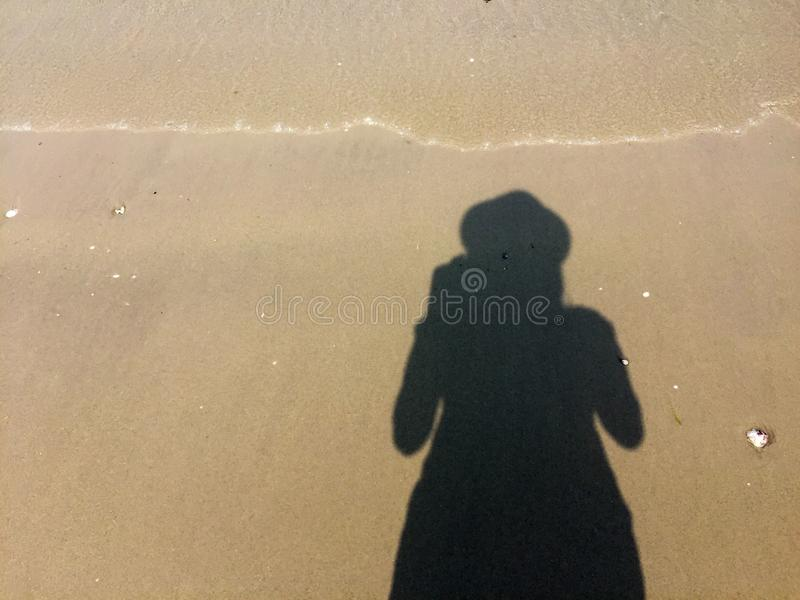 Girl photographer`s shadow on the sand royalty free stock image