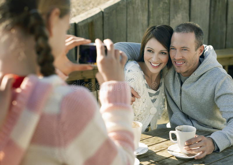 Girl Photographing Parents At Outdoor Table stock photo