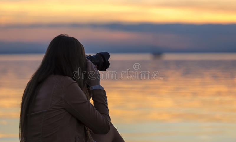 Girl photographing sunset. At lake in autumn royalty free stock images