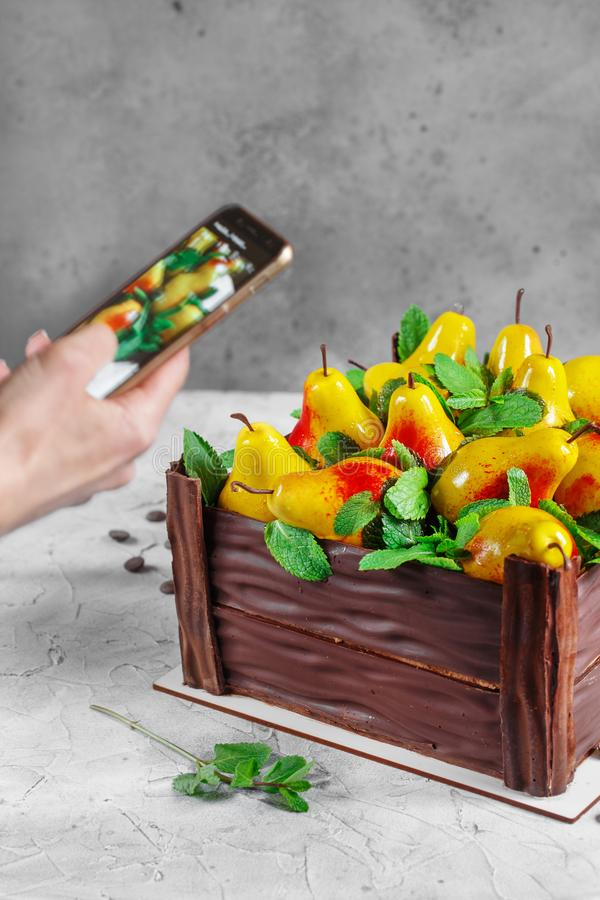 Girl photographs a pear cake with a smartphone. Birthday cake in the form of a chocolate box filled with pears made from mousse stock photo