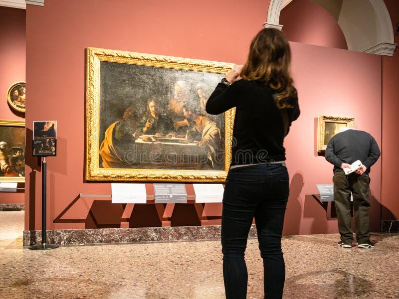 Girl photographs picture in Pinacoteca di Brera. MILAN, ITALY - FEBRUARY 24, 2019: girl photographs picture in Pinacoteca di Brera Brera Art Gallery in Milan stock images