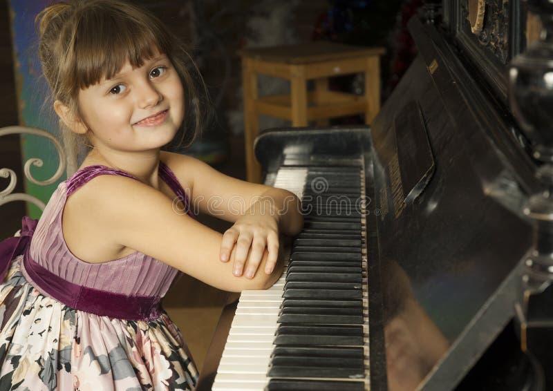 Girl and piano royalty free stock photos