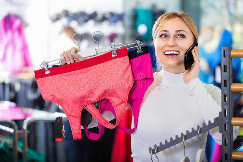 Girl picking a sport bra while talking to the phone royalty free stock photos