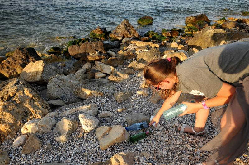 Girl picking up garbage left on a beach in Romania stock photo
