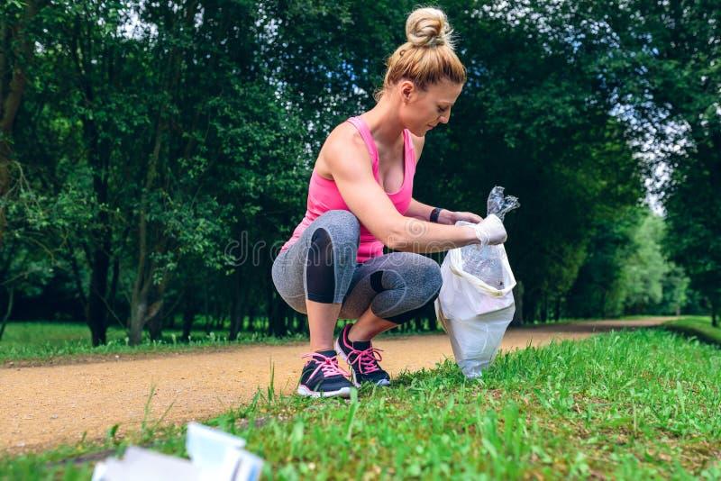 Girl picking up trash doing plogging royalty free stock image
