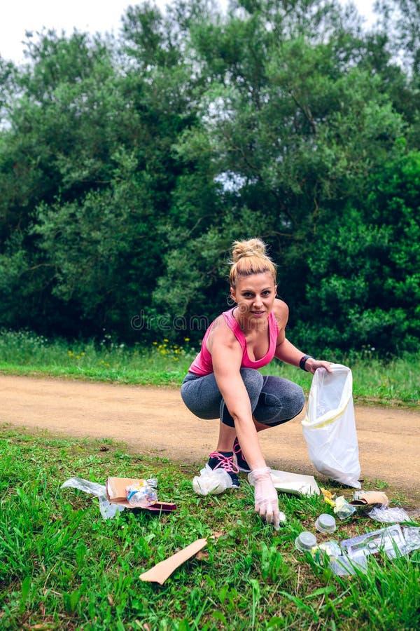 Girl picking up trash doing plogging royalty free stock photography