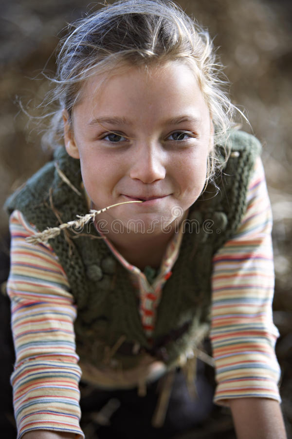 Girl (9-11) with piece of straw in mouth, smiling, close-up, front view, portrait stock image