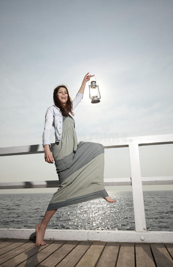 Download Girl On Pier With Kerosene Lamp Stock Photography - Image: 33735582