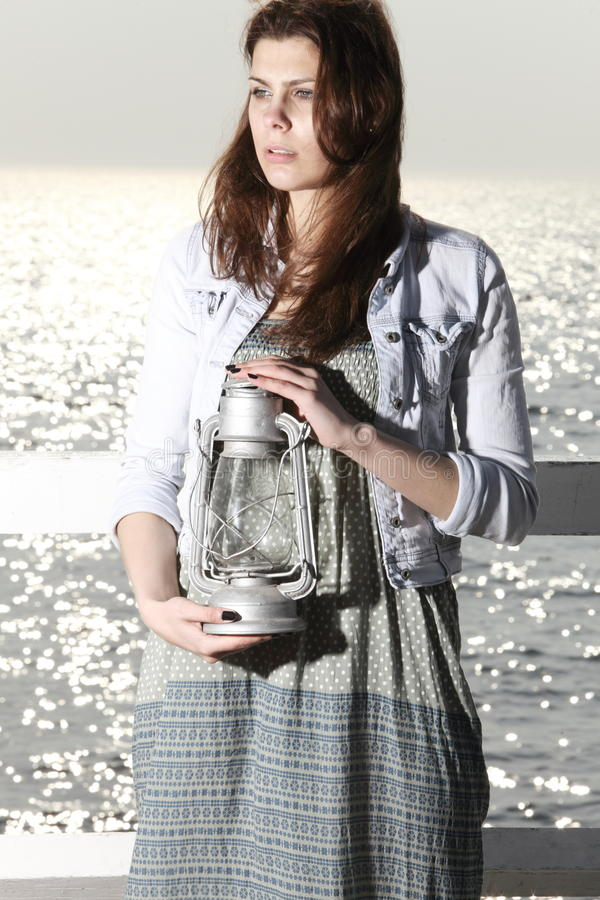 Girl On Pier With Kerosene Lamp Stock Photography