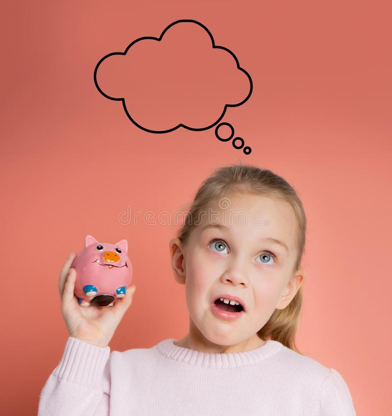 Girl with a piggy bank on a pink background stock photos