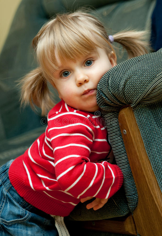 Girl with pigtails. Portrait of a cute little blond girl with pigtails, leaning against a sofa or couch royalty free stock images