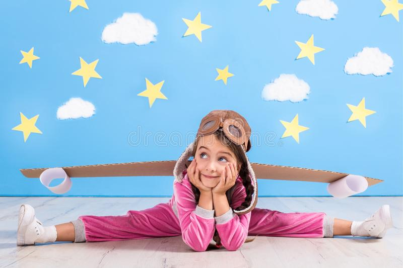 Girl pilot playing with toy jet pack at home. Success and leader concept. Kid on the background of bright blue wall with white clouds and yellow stars royalty free stock image