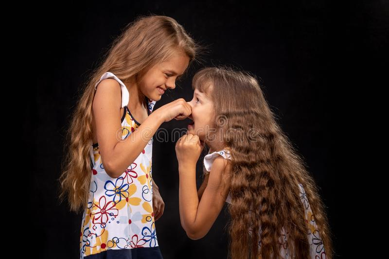 Girl pinched a hand on the nose of another girl. Girl pinched a hand on the nose of another  girl royalty free stock images