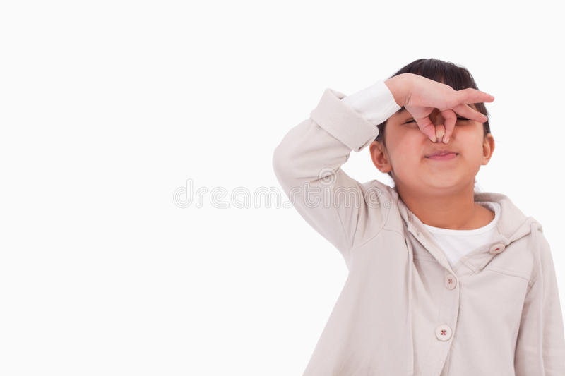 Girl pinching her nose. Against a white background stock photo