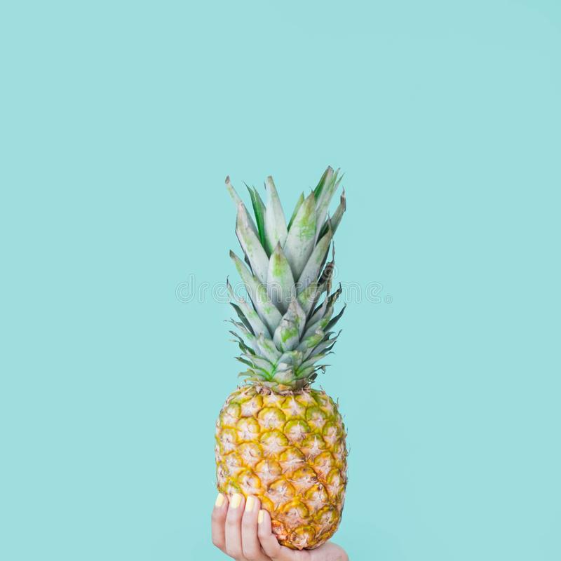 Holding a pineapple. Yellow nails. Girl hands. stock photos