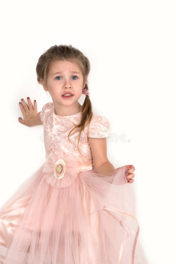 The girl in a pink ball dress and with blue eyes stands at a wall. She is frightened. stock photography