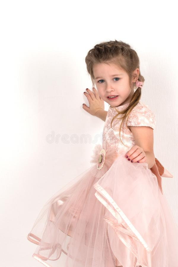 The girl in a pink ball dress and with blue eyes stands at a wall. She smiles. royalty free stock image