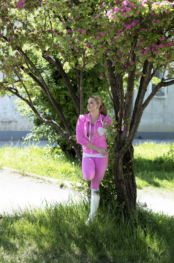 The girl in pink at the blossoming pink tree. Spring royalty free stock photo