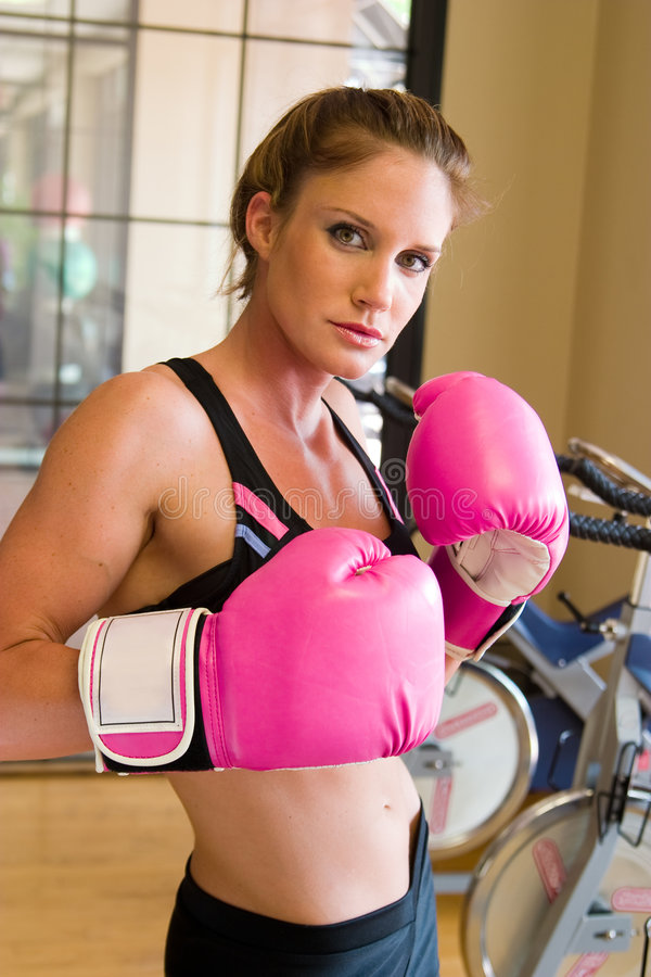 Girl In Pink Boxing Gloves 2. Beautiful, fit woman wearing hot pink boxing gloves royalty free stock photos