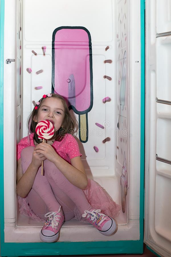 Girl in pink clothes with a Lollipop. In the background, a variety of sweets. royalty free stock photo