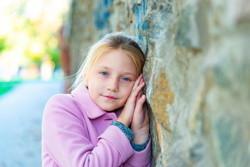 A girl in a pink coat stands near the wall, rubbing close-ups. stock photography