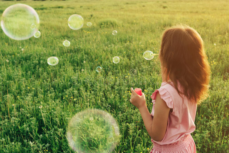 Girl in pink dress blowing soap bubbles in summer. Little girl in pink dress blowing soap bubbles on summer meadow, face is not visible. Image with sunlight stock image