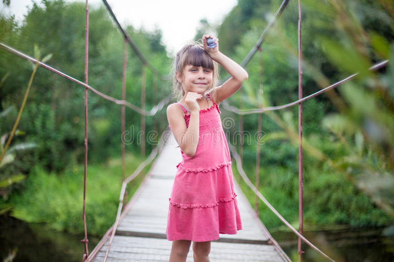 The girl in the pink dress on the bridge. Village stock image